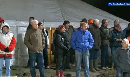 Tientallen geïnteresseerden kijken 's avonds naar de operatie.