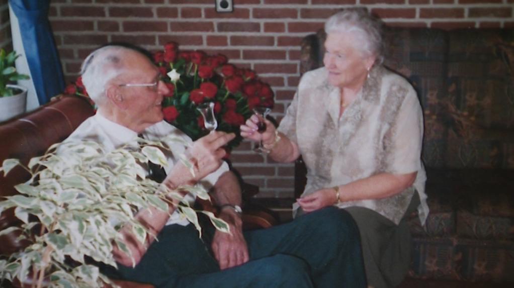 Foto: Jan Thus en Miep. Op de achtergrond de bos met 60 rozen ter ere van hun60-jarige vriendschap.